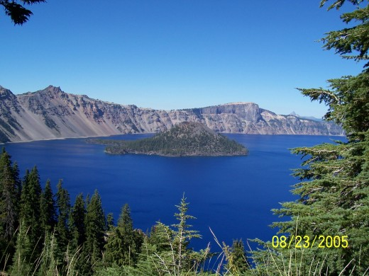 View of Wizard Island through trees at Crater Lake.