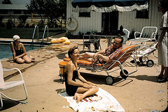 MAKING THE SCENE AT THE POOL. THIS EASY-GOING, WELL-PAID PLAYBOY HAS IT MADE WITH HIS PRETTY DATE, HIS CHAISE LOUNGE AND A SUNNY DAY.