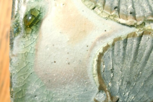 Detail of the surface of a piece of wood fired pottery. Note the fluid runs and pools of the green glassy ash glaze. Potter: Svend Bayer, UK