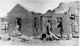 "The building of ""The Bottle House"" in 1906. It is believed that Tom Kelly is the man in the doorway."