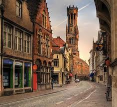 Tall and narrow buildings neatly lined up to the street are typical in the older sections of historical Belgium.  Some are triangle topped, others have a crown to signify the royal government.  Rain or shine, bicycles are a popular form of transport