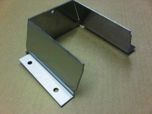 Stainless steel sheet metal angle bracket part of a much larger stainless housing assembly.