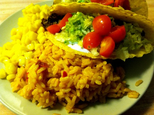 Vegetarian tacos served with Spanish rice and sweet corn