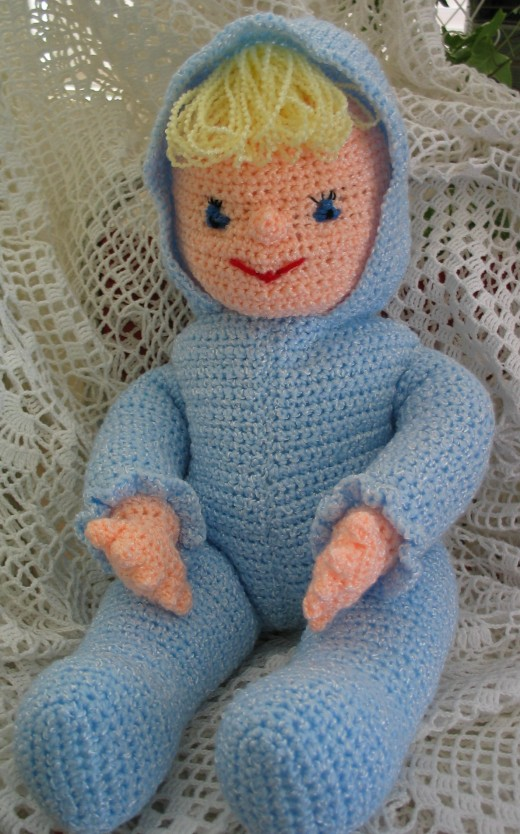 CROCHETED DOLL WEARING BLUE by Jprescott DESCRIPTIONA crocheted doll toy with blonde hair wearing a blue suit with a hood.