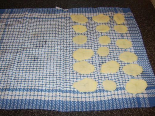 Potato discs are patted dry in a clean tea towel