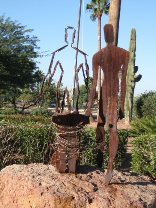 Sculpture of 3 Vietnam War POWs - Ghost of One, POW standing & one kneeling with barbed wire.