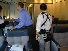 News photographers claim their seats in the press cabin of Air Force One.