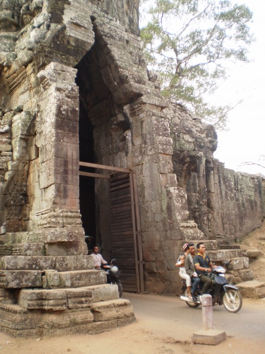 Vehicles go through the South Gate of Angkor Thom.