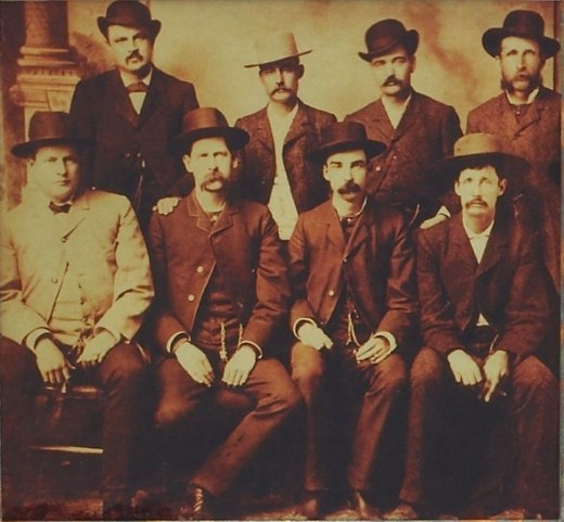 This photo was published pre-1923. From left to right, standing: W.H. Harris, Luke Short, Bat Masterson, W.F. Petillon. Seated: Charlie Bassett, Wyatt Earp, Frank McLain and Neal Brown