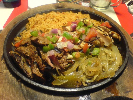 A mixed platter of beef and chicken fajitas with onions and rice