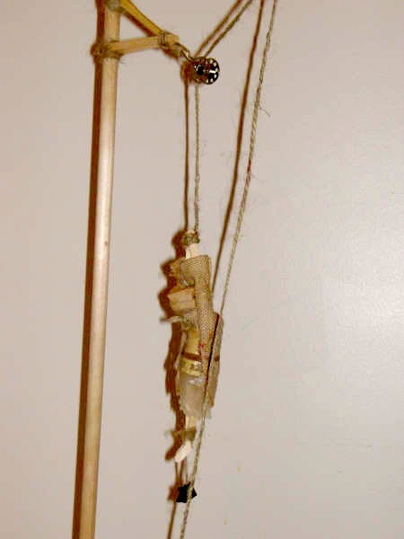A thread pulley is used, twine and a clip.
