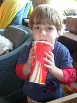 Child Drinking From Large Paper Cup. Soda Pop?