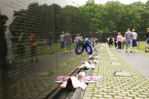 It is common to see flowers and flags left at the Wall to honor victims of the war.