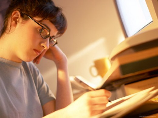 Student Taking Notes While Studying at Her Desk