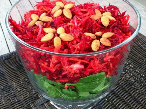 Shredded Carrot, Beet, & Apple Slaw served on a bed of baby spinach & topped with almond flowers.