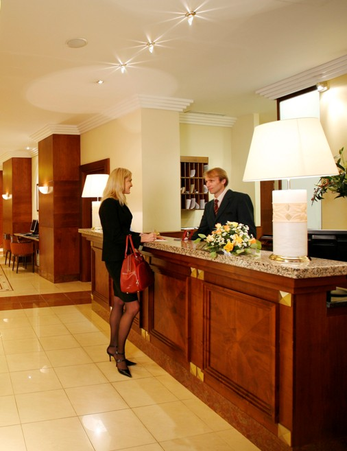 Young woman checking in at front desk of a hotel