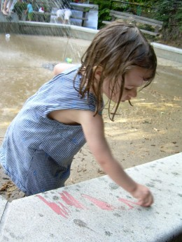 Young artist at the water fountain in the summer