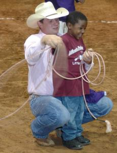 Photo by Jim Williamson. Shaun Smith helped a young cowboy learn how to rope at the Four States Fairgrounds.
