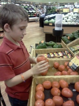 Invite your children to menu plan, make shopping lists.  Here, my oldest son looks for bruising on a tomato.  We know organic and home grown taste the best and offer the greatest nutritional value.