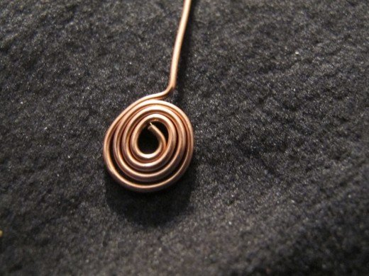When the spiral is completed, bend the wire to create a stem over it.