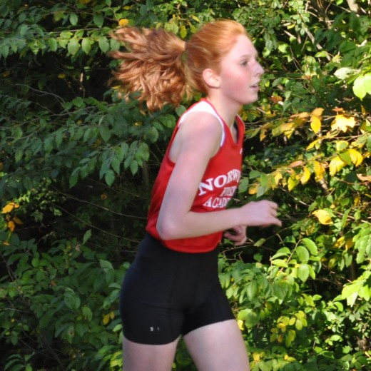 Michaela running in a cross country race in high school.