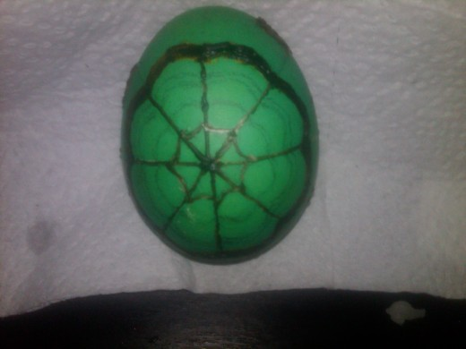 Green egg with yellow outlines covered in wax