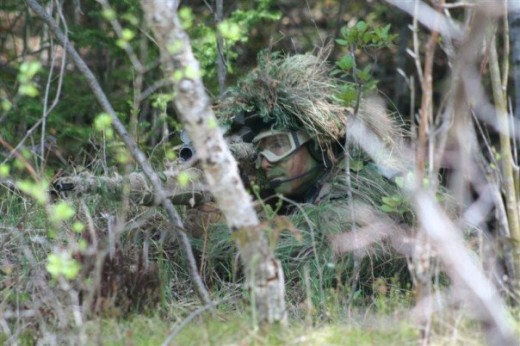 An airsoft sniper wearing a ghillie suit.