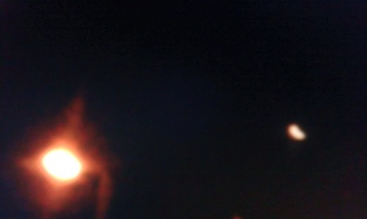 The huge light on the left is a streetlamp, it's the object on the right which is unidentified.