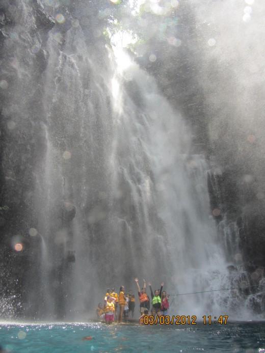 raft under the gushing Tinago Waterfalls