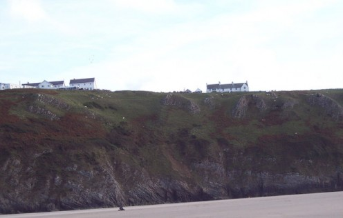 Cliffs at Rhossili Bay. Taken from the beach, showing the Worms Head National Trust Visitor Centre on the right.