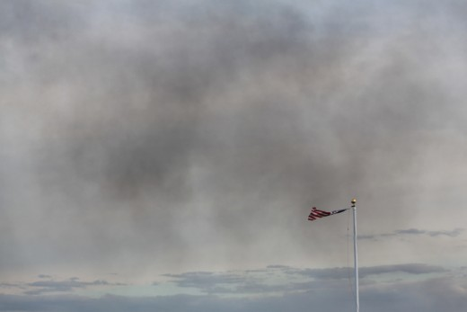 smoke from brush fire passing the American Flag blowing in the wind on rock at Anchor Beach in Milford, CT on 4/9/12