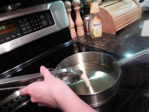 Fry churros in saucepan.