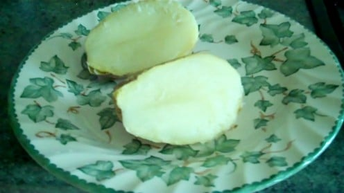Baked potato, fresh out of the microwave, sliced in half.