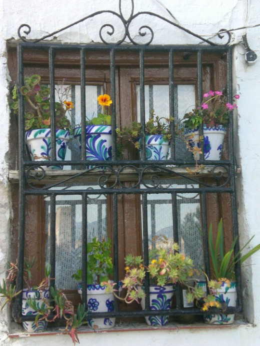 Flower pots in window in Granada, Spain