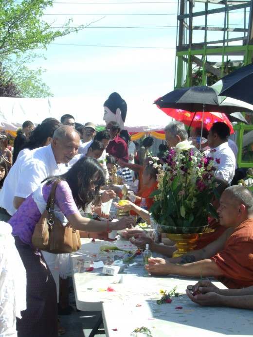 Holy Water festival; cleaning the palm of a monks hand, Buddha statue, and parent asking for forgiveness and a restart of life.