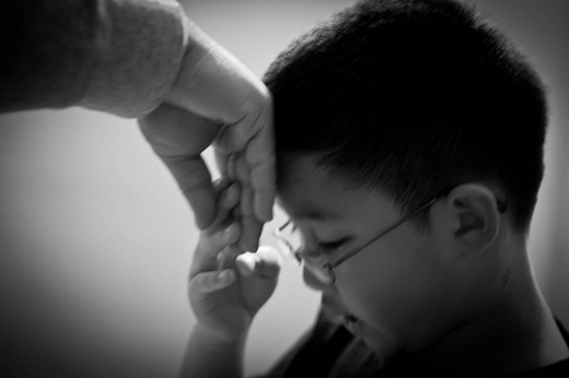"The act of Filipino tradition, ""mano"" where the kid put the elderly's back of the hand into his forehead in which a response of ""God bless you"" would be said."