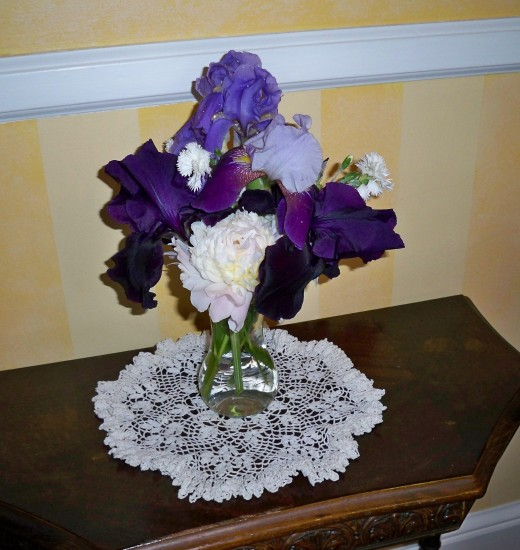 Peonies, black iris, Russian iris, common iris, and carnations in a vase.