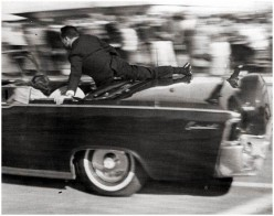 Secret Service agent Clinton Hill nestling against the fastback of the presidential limousine after JFK was shot. November 22, 1963.