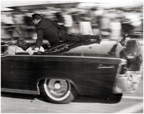 Secret Service agent Clinton Hill nestling against the fastback of the presidential limousine after JFK was shot. November 22, 1963.