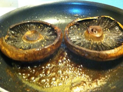 Portobello mushrooms cooking in Earth Balance