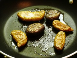 Fingerling potatoes being sautéed after being briefly microwaved and smashed by hand to flatten them out.  Could also be sliced in half instead.