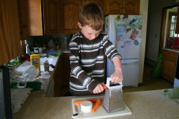 My six year old son grates carrots.