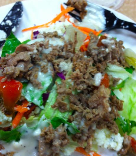 Grilled steak on top of a greek salad.