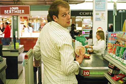 """""""What? You want me to mop the vomit in aisle 87?"""" quieries this male cashier as he is in the middle of checking-out a customer."""