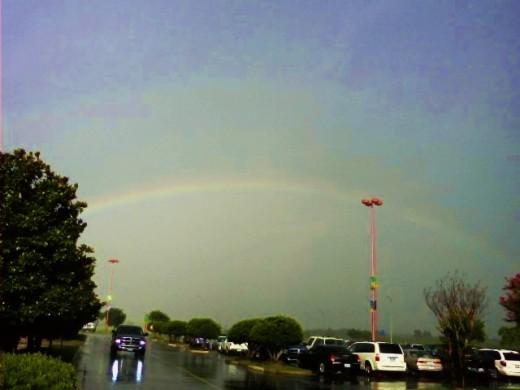 A double rainbow with a bold primary rainbow and a very faint secondary rainbow.