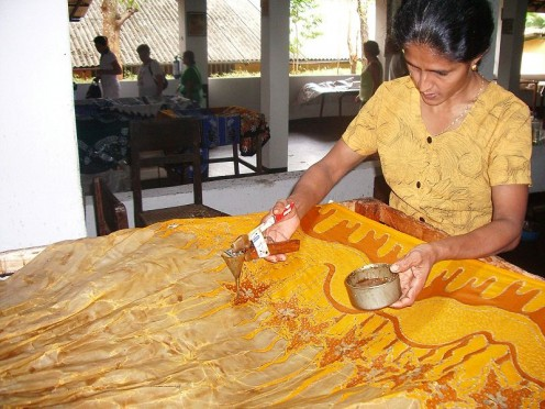A batik artist at work, using a canton, also known as a wax pen.