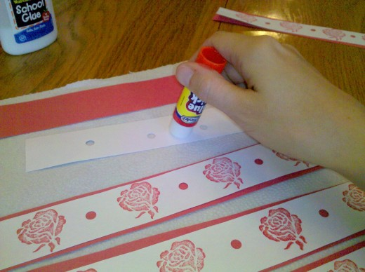 Use white glue or a glue stick to attach the white strip of paper to the red strip.
