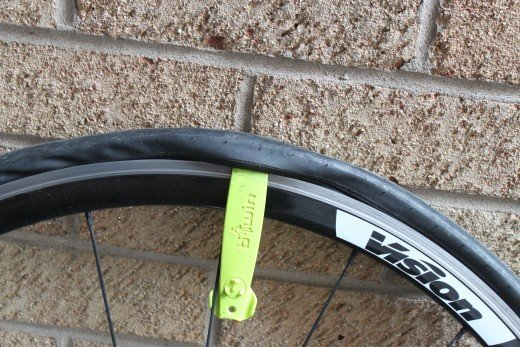 Pull the tire lever down to unhook the tire bead and if possible hook the tire lever around a spoke