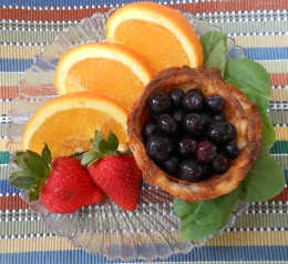 Fresh blueberries in a biscuit cup: Garnished with baby spinach, sliced oranges and fresh strawberries.