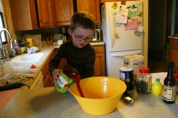 My four year old pours the tomato sauce into a large mixing bowl.